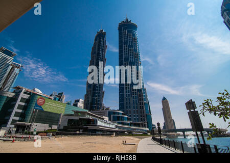 Dubai, United Arab Emirates - October, 2018: Modern skyscrapers and water channel with boats of Dubai Marina at sunset - Stock Photo