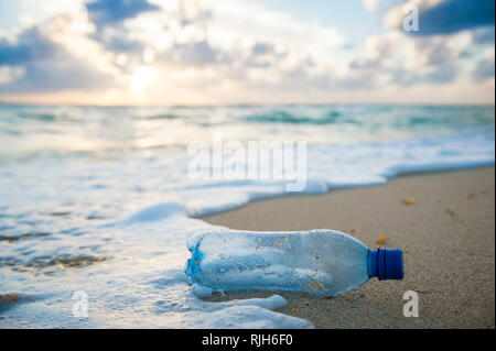 Used plastic water bottle washed up on the shore of a tropical beach, highlighting the worldwide crisis of plastic pollution on even remote islands - Stock Photo