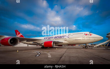 Virgin Atlantic Boeing 747-400 Jumbo Jet waiting on the apron at Gatwick Airport at dusk. - Stock Photo