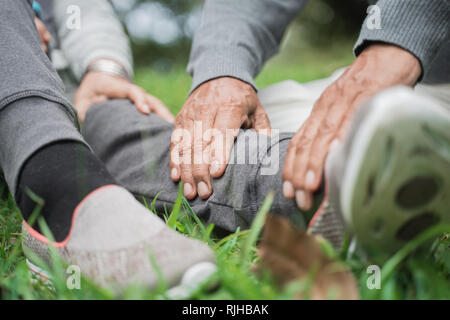 senior's hand giving massage on leg - Stock Photo