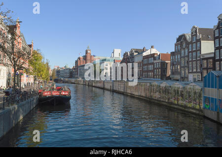 Amsterdam, The Netherlands, October 10, 2018: View of the market stalls of flower market and bicycle parking made on barge - Stock Photo