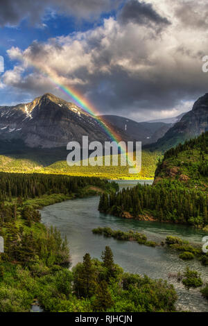 A rainbow creates a gateway for the Swiftcurrent river into Sherburn Lake in Many Glacier. - Stock Photo