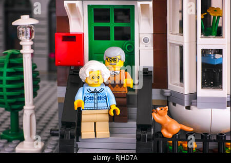 Tambov, Russian Federation - October 18, 2017 Lego senior couple standing on porch of their house with his ginger cat. Studio shot. - Stock Photo
