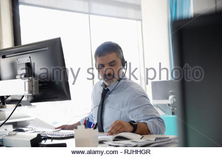 businessman with headset working at computer in office - Stock Photo