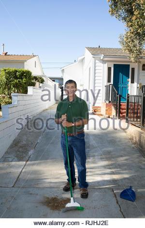 Portrait confident Latinx senior man sweeping driveway - Stock Photo