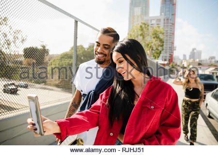 Latinx couple taking selfie with smart phone on urban overpass - Stock Photo
