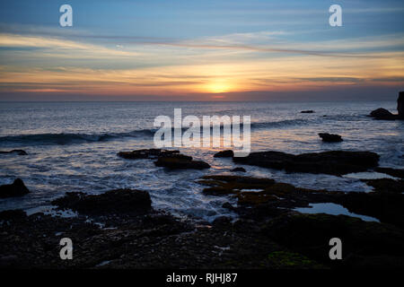 Sunset over ocean at Tanah Lot, Bali, Indonesia - Stock Photo