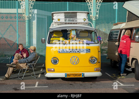A couple sits chatting next to a yellow painted Volkswagen VW campervan on Madeira Drive in Brighton, Sussex, England. - Stock Photo