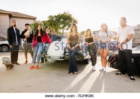 Portrait confident, cool Latinx friends in parking lot with vintage car - Stock Photo