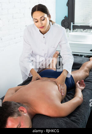 Professional masseuse performing back massage to positive american male client in spa center - Stock Photo