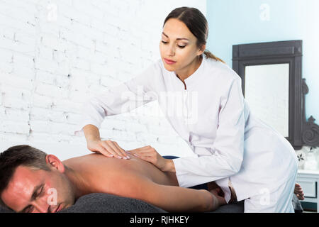 Professional masseuse performing back massage to positive male client in spa center - Stock Photo