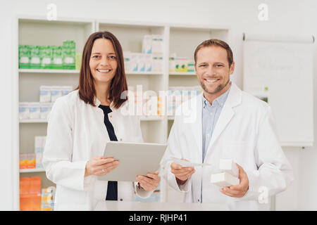 Two happy friendly pharmacists in a pharmacy standing holding medications and scripts smiling at the camera - Stock Photo