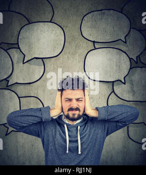 Frustrated stressed man covering with hands his ears tired of too much talk around him - Stock Photo