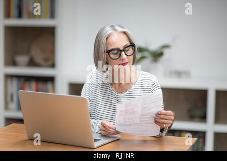 Mature adult female paying bill online using a laptop - Stock Photo