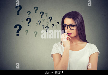 Portrait confused thinking woman bewildered seeks a solution looking preoccupied has many questions isolated on gray wall background - Stock Photo