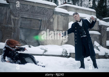 Battle of dark and light magicians with the help of magic wands and green beam on the snow background. - Stock Photo