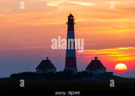 The lighthouse Westerheversand at sunset. Peninsula of Eiderstedt, North Frisia, Germany - Stock Photo