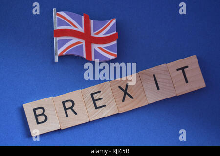 Creative Concept : British politics : 3d Union Jack flag and the word Brexit isolated on a blue background - Stock Photo