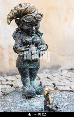 One of the brass gnomes (krasnale, krasnoludki), a photographer taking a photograph of a miniature gnome, in Wrocław, Wroklaw, Poland - Stock Photo