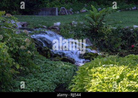 The photographer captured a smooth milky effect with this small waterfall surrounded by greenery on a bright sunshinny day in a Missouri park. - Stock Photo