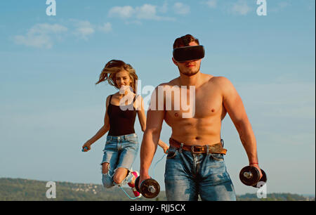 Strong man with musucular torso and fit woman skipping. Strong sportsman use smart technology for building muscle. Strong bodybuilder wear vr headset - Stock Photo