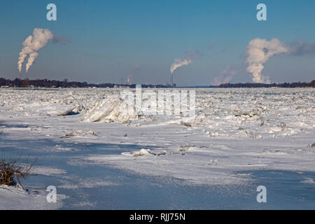 Marine City, Michigan - DTE Energy coal-fired power plants line the U.S. side (left) of the ice-filled St. Clair River. The Canadian side has mostly r - Stock Photo