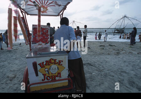 Caption: Fort Cochin, Kerala, India - May 2003. An ice-cream vendor waits for customers on the beach at Fort Cochin, the touristy Portuguese town on I - Stock Photo