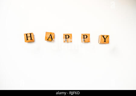 Vintage Wooden Stamps Spelling Happy on White Background With Copy Space - Stock Photo
