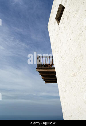 Perspective view from below of an older white typical building with a wooden balcony and a window, in the background the ocean and blue sky - Location - Stock Photo