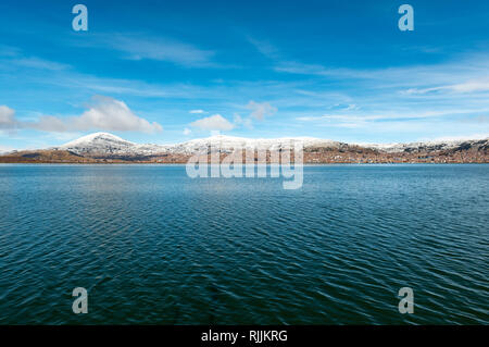 Cityscape of Puno city in the snow in the altiplano of Peru and the Andes mountain range with the blue waters of the Titicaca lake, South America. - Stock Photo