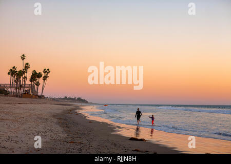 Mother and daughter walking San Clemente State Beach at Dusk - Stock Photo