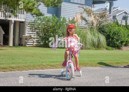 Little girl learning to ride a bike with training wheels. - Stock Photo