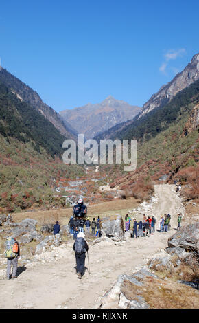 a crowd gathers near a rescue helicopter in the Tamur valley of eastern Nepal as trekkers pass on a new road - Stock Photo