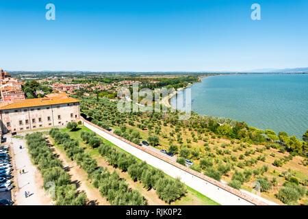 Castiglione del Lago, Italy - August 28, 2018: Umbria Rocca with Medievale o Rocca del Leone and lake Trasimeno in sunny summer day with olive trees a - Stock Photo