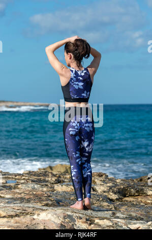 sports woman tying her hair up preparing to run and exercise by the sea in the sun - Stock Photo