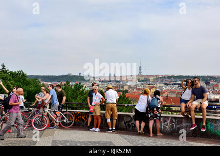 People looking at the view over Prague from the top of Letna Hill by the Prague Metronome, the old Stalin culture centre park Stock Photo