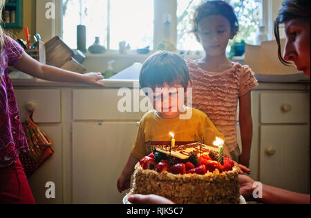 Smiling young boy and his two sisters admiring the birthday cake their mother has made for him.