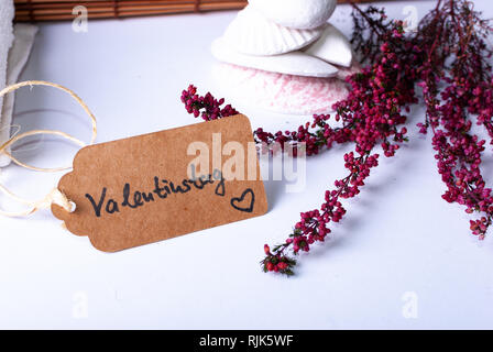 A label saying 'Valentinstag' and colorful red branches, stones, candles and a bamboo mat on white background with copy space - Stock Photo