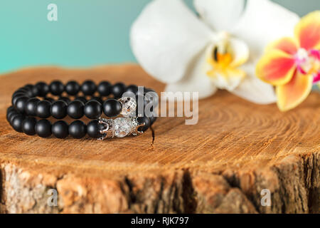 Exquisite women's bracelets made of natural stones, agate and sugar quartz with accessories that are encrusted with cubic zirconias. Close-up. Studio  - Stock Photo