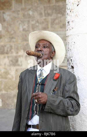 Havana, Church Square - Cuba - A Cuban man with white cowboy hat and stylish outfit, watching the surroundings with cigar in his mouth - Stock Photo