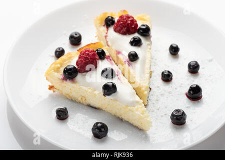 Cheesecake with cream and fresh raspberries and blueberries on a white plate. - Stock Photo