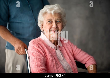 Senior woman being pushed in a wheelchair. - Stock Photo