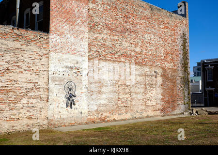 Likeness of Dr Martin Luther King Jr (MLK) painted on the side of an old brick wall in a vacant lot in downtown Montgomery Alabama, USA. - Stock Photo