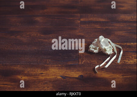Close-up of cute baby shoes on a wooden background. Stylish children's shoes. White children's shoes on a dark background place for text. Concept chil - Stock Photo