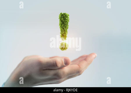 Hand of businessman holding green exclamation mark - Stock Photo