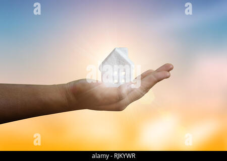 Mortgage concept by new small house in hand have rays of the sun fantastic and housing a young family or protection of property, for sale or rent, mod - Stock Photo