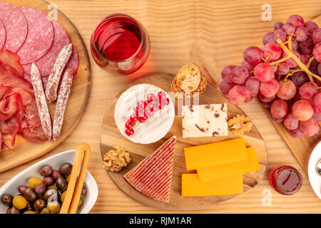 A charcuterie platter and a cheese board, sausages and hams, and a glass of red wine, shot from the top on a wooden background with copy space - Stock Photo