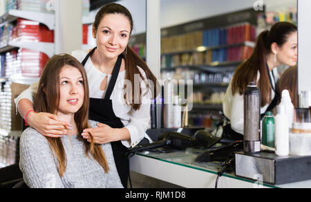Young pleasant cheerful positive  female hairdresser with male visitor in beauty salon - Stock Photo