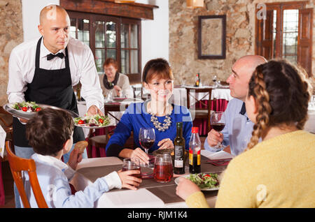 Cheerful waiter serving plates of salad to happy family having dinner at restaurant - Stock Photo