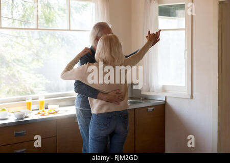 Aged couple husband and wife dancing in the kitchen - Stock Photo